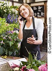 kobieta, pracujący, kwiaciarnia, używając, telefon, i, uśmiechanie się