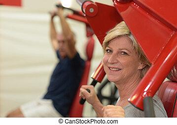 kobieta, senior, podnoszenie, sala gimnastyczna, dumbbells