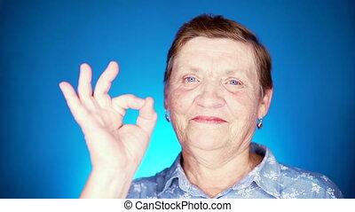 kobieta, -, tło., błękitny, pokaz, kaukaski, portret, gest, aparat fotograficzny, approval., uśmiechanie się, babcia, patrząc, ok, piękny, znak, sędziwy