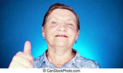 kobieta, -, tło., błękitny, pokaz, kaukaski, portret, gest, aparat fotograficzny, approval., uśmiechanie się, babcia, patrząc, piękny, znak, sędziwy, kciuk-do góry
