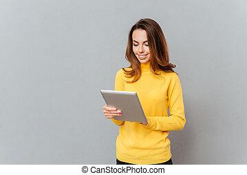 kobieta, tabliczka, sweter, młody, żółty, komputer, używając, uśmiechanie się