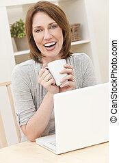 kobieta używający laptop, komputer, w kraju, pijąca herbata, albo, kawa