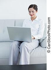 kobieta, ubrany, laptop, dobrze, sofa, używając, uśmiechanie się