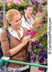 kobieta, w, ogrodowy środek, przeglądnięcie, kwiaty