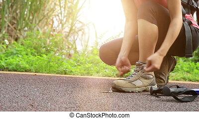 kobieta, wycieczkowicz, młody, wiążąc shoelaces
