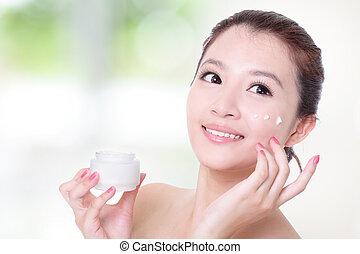 kobieta, zwracający się, jej, twarz, moisturizer, śmietanka