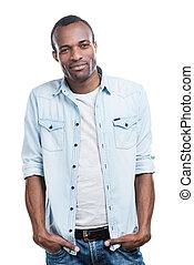koel, en, carefree., mooi, jonge, zwarte man, holdingshanden, in, zakken, en, het glimlachen, aan fototoestel, terwijl, staand, tegen, witte achtergrond