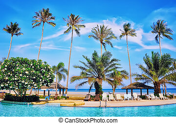 Koh Samui summer resort, turquoise swimming pool, blue sea and palm trees in Thailand