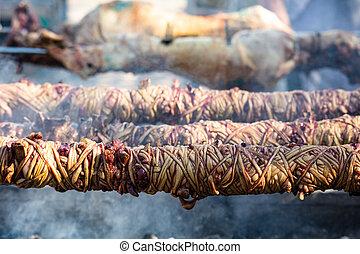 Kokorec and lamp spits on coals fire. Greek Easter,...