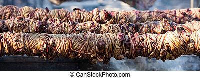 Kokorec spits on coals fire, banner. Greek Easter,...