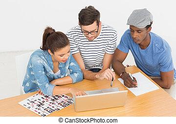 koncentrerat, konstnärer, arbeta på, laptop, på kontoret
