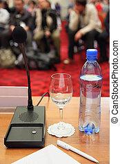konferenz, in, hall., flasche, mikrophon, glas, und, stift, auf, a, tisch., fokus, auf, wasser, in, glas.