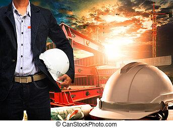 konstruál, ember, noha, fehér, biztonság sisak, álló, ellen, dolgozó, asztal, és, épület szerkesztés, színhely