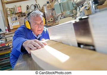 konzentriert, älterer mann, zimmermann, schneidenden holz, mit, tablesaw, in, werkstatt