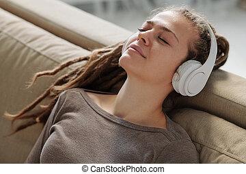 kopfhörer, m�dchen, beruhigen, musik, couch, lächeln, entspanntes, zuhören, während