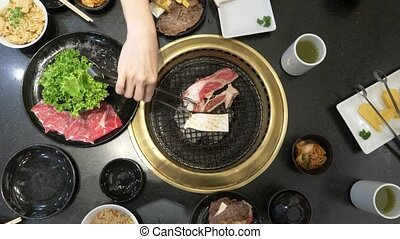 Korean barbecue grill. people cook and eat dishes cooked on...