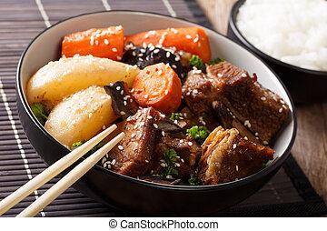 Korean Braised Beef Short Ribs with rice garnish close-up....