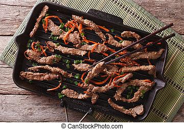 Korean bulgogi beef with carrot on grill pan. horizontal top...