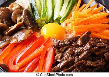 Korean cuisine: Bibimbap with beef, raw yolk, vegetables and...