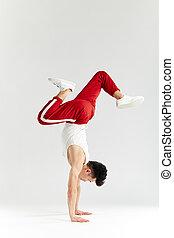 Korean dancer executes basic freezes of downrock brea dance isolated on white