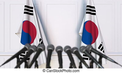 Korean official press conference. Flags of South Korea and...