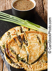Korean pancakes Pajeon with green onions close-up on a slate...