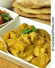 Closeup of chicken pieces in korma spices