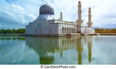 Kota Kinabalu City Mosque, with its beautiful and famous, blue and gold dome and minarets, stands against a cloudy sky over Likas Bay on Borneo Island in Malaysia.