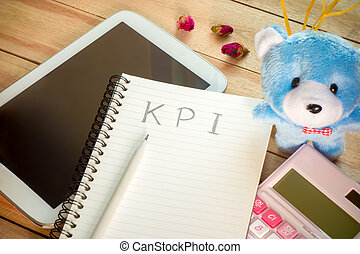 KPI list notebook with tablet calculator pencil on wood floor , digital effect vintage style