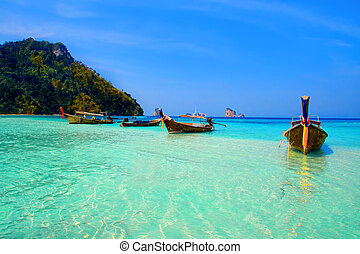Krabi - Longtailboats tied up in the turquoise waters at...