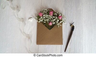 Kraft envelope with flowers on a wooden white background...