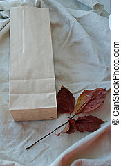 Kraft paper bags with autumn leaves on vintage linen fabric background.