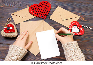 kraft paper envelope with wooden red heart on wooden table with copy space