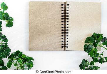 Kraft paper spiral notebook with green leaves as frame