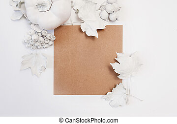 kraft sheet of paper, white pumpkin, berries and leaves on a wooden background. mockup autumn. Greeting card for Thanksgiving Day in rustic style with space for your text. Flat lay. Top view