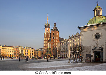 Late afternoon in the main square (Rynek Glowny) in the old town district of Krakow in Poland. View of the Church of St. Mary, St. Adalbert's Church and the Statue of Adam Mickiewicz.