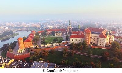 Krakow, Poland. Wawel royal Castle and Cathedral, Vistula River. Cracow old city with historic churches in the background. Aerial 4K flyby video at sunrise in summer