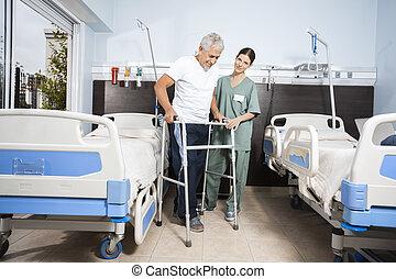 krankenschwester, assistieren, älter, patient, in, gebrauchend, gehhilfe, an, reha, zentrieren