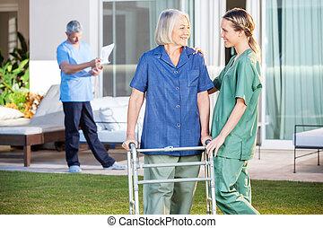 krankenschwester, assistieren, ältere frau, gehen, mit, zimmer rahmen