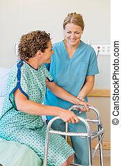 krankenschwester, assistieren, patient, gebrauchend, gehhilfe, in, klinikum