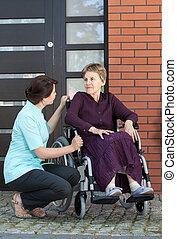 krankenschwester, sprechende , mit, ältere frau, auf, rollstuhl