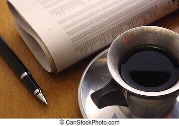 krant, pen, zwarte koffie