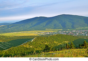 Green hills under blue sky in village district of Krasnodar krai in summer
