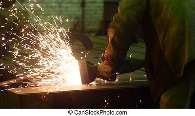 Krasnodar, Russia - 01.25.2018: Welder works circular saw, cuts metal. Flies of spark from hot metal. In slow motion