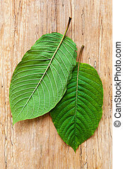 Kratom leaves on wooden table from above.