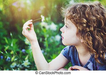 krullend, baby met, bloemen, in, haar, hand., verstevigend, photo.