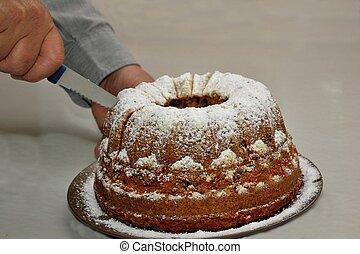 Kuchen wird angeschnitten - Gugelhupf wird von Person ...