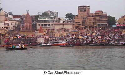 Wide low-angle dolly shot from Ganga River of Kumbh Mela pilgrims and devotees gathered at Munshi Ghat Temples, Varanasi, Ganges