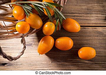 Kumquat berries on wooden background. Citrus fruit ingredient food.
