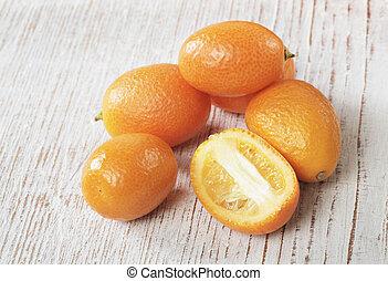 Kumquat - Small orange kumquat fruit on wood.